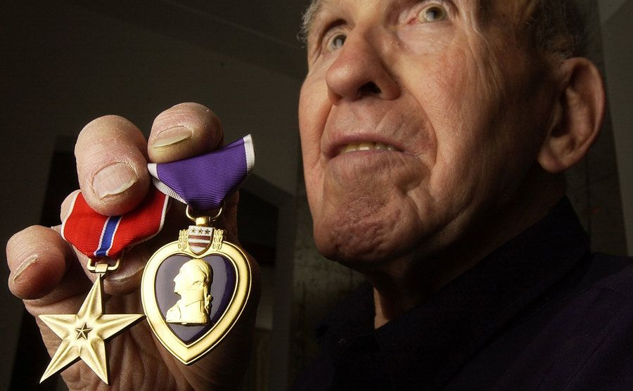 A war veteran shows off his purple heart and bronze star for bravery.