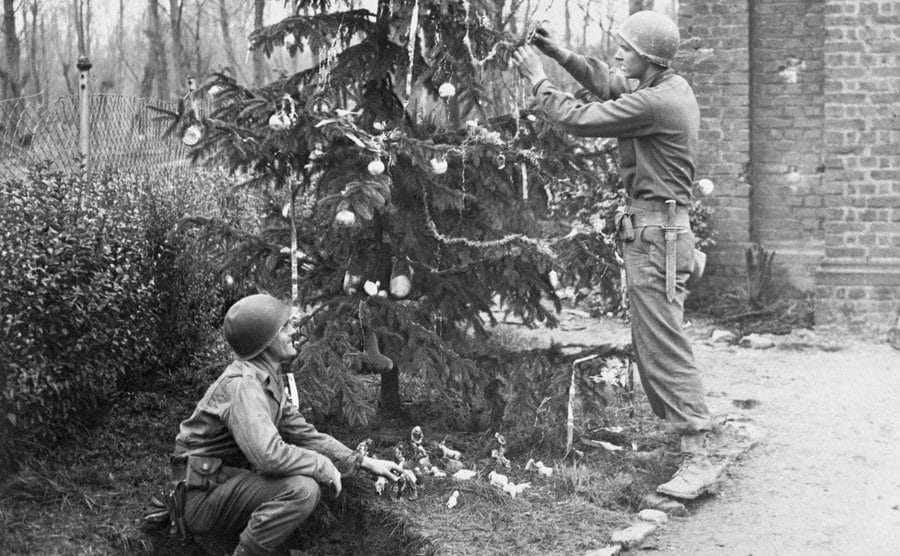 Soldiers decorate a Christmas tree.