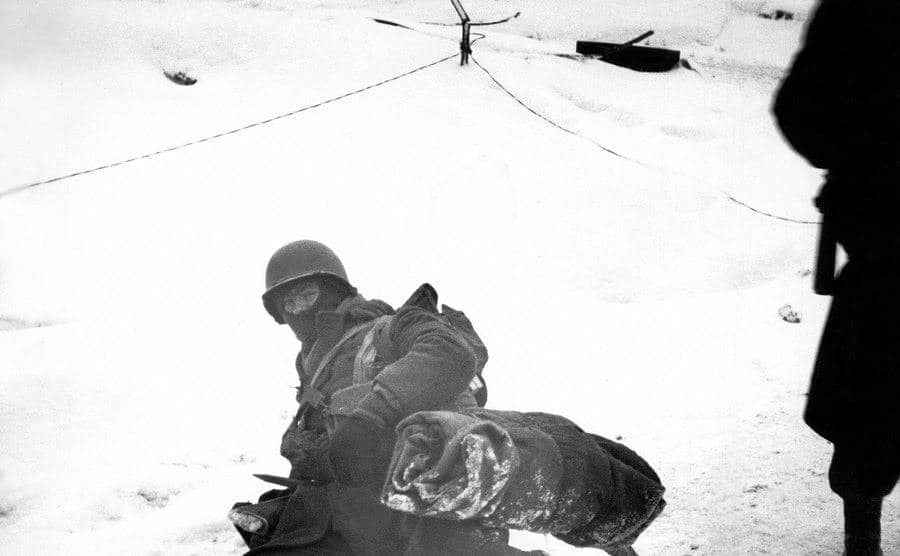 A soldier lays down on the snow during the Battle.