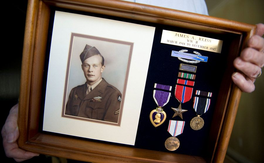 An old picture of a war veteran and his medals.
