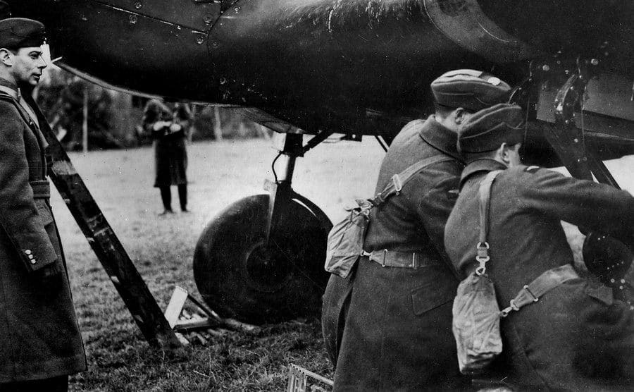 Aircraft men are checking a plane.
