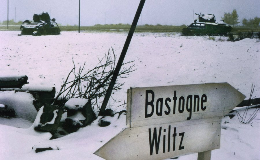 Tanks in the snowy field and a sign that reads ''Bastogne Wiltz.''