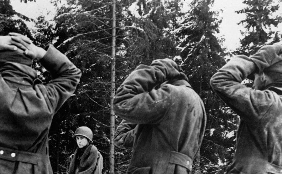 An American soldier holds German prisoners at gunpoint.