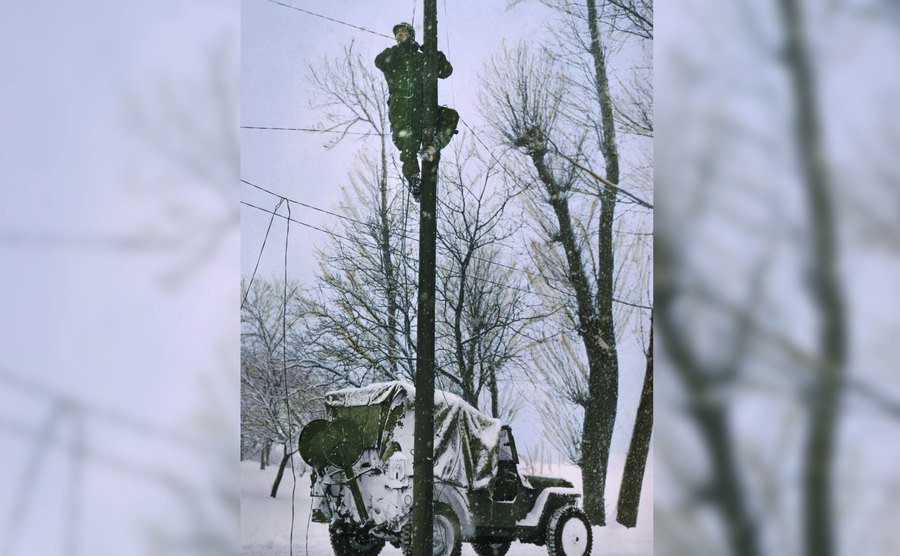 A soldier repairs a damaged telephone line in Ardennes.
