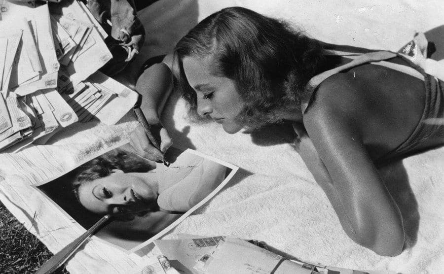 Joan Crawford signs autographs while sunbathing.