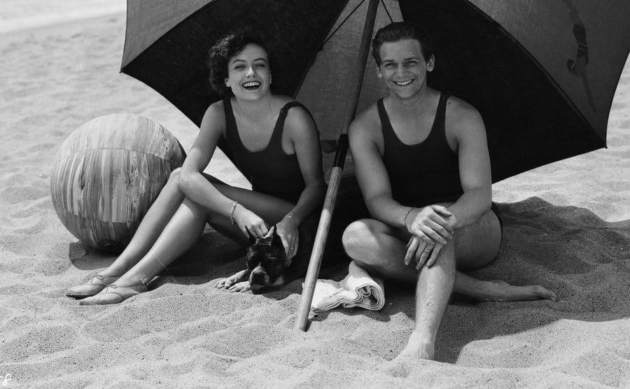 Joan and Doug share the shade of a large beach umbrella.
