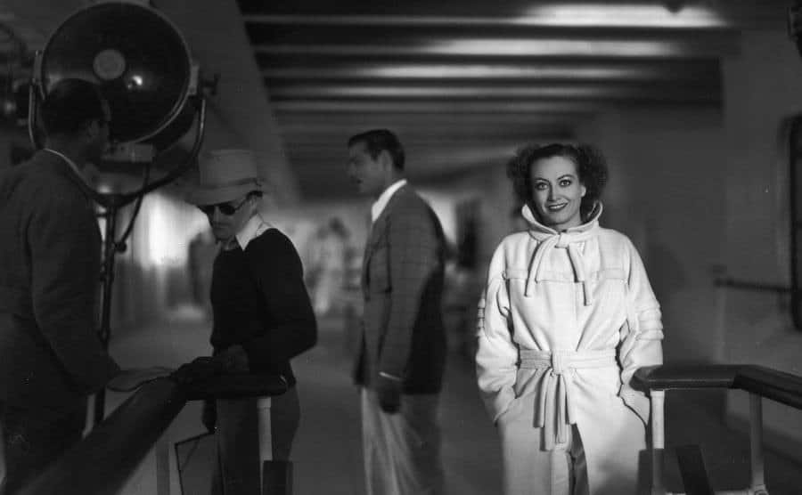 Joan Crawford smiles at the camera on a movie set.