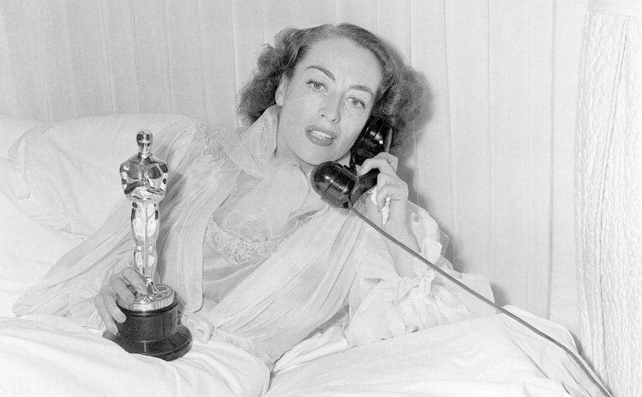 Crawford holds her Academy Award while lying in bed and talking on the phone.
