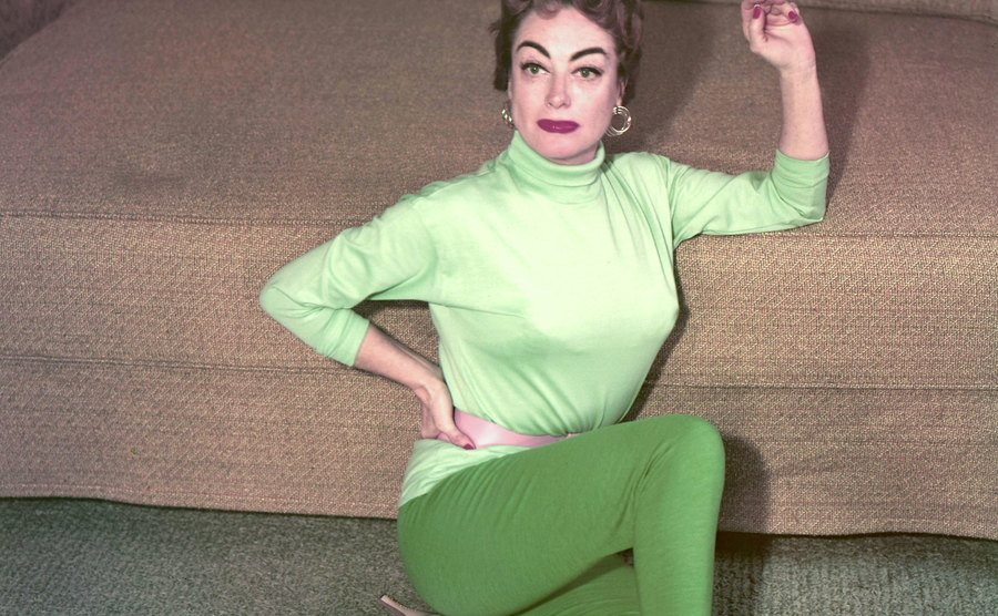 Joan Crawford sits on the floor next to a sofa.