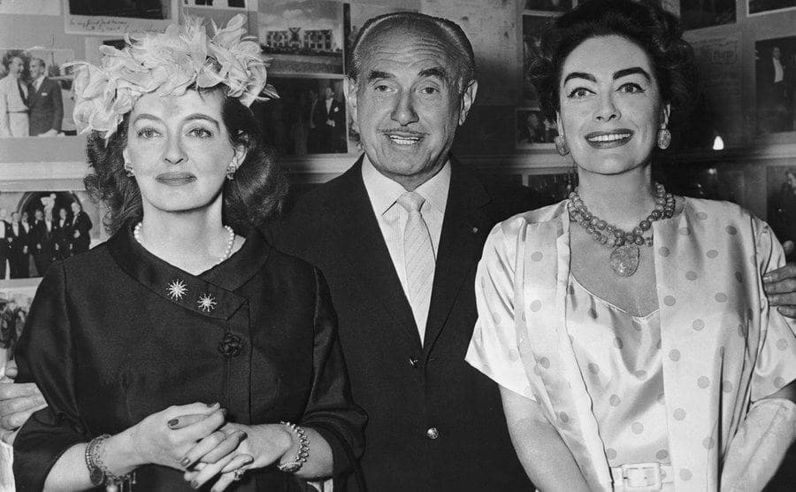 Bette Davis, Jack L Warner, and Joan Crawford pose for a picture.