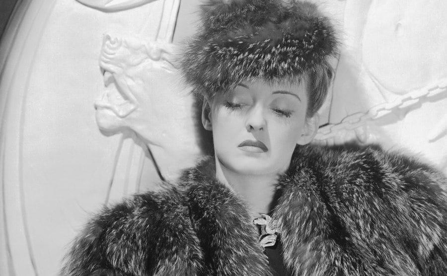 A portrait of Bette Davis wearing a fur coat and hat.
