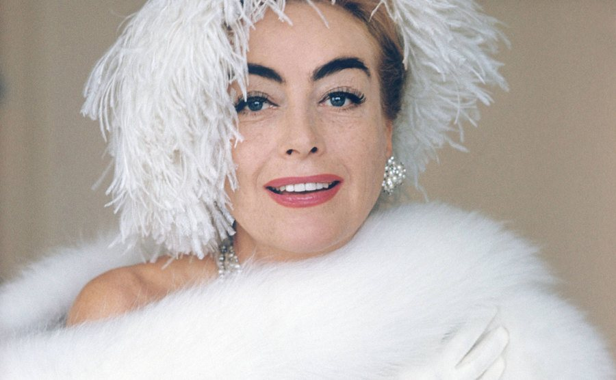 Joan Crawford poses wrapped in white fur.