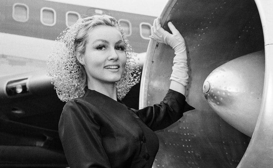 Julie Newmar is standing beside a jet engine.