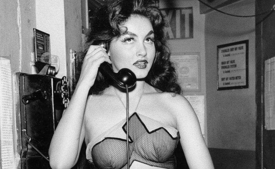 Julie Newmar makes a phone call during a Broadway stage production.