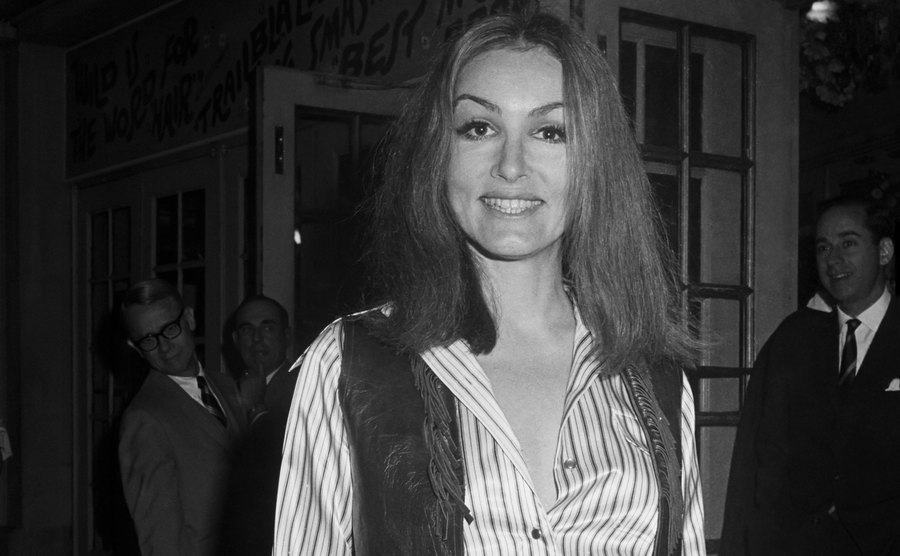 Julie Newmar is standing outside a theater.
