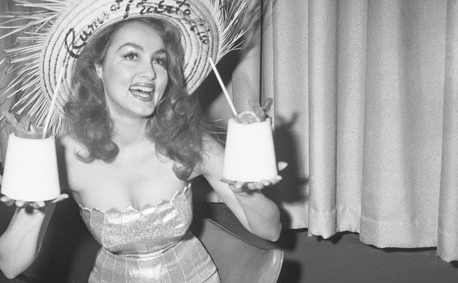 Julie Newmar is smiling after being crowned Queen of the Hotel New Yorker's Rum Fiesta.