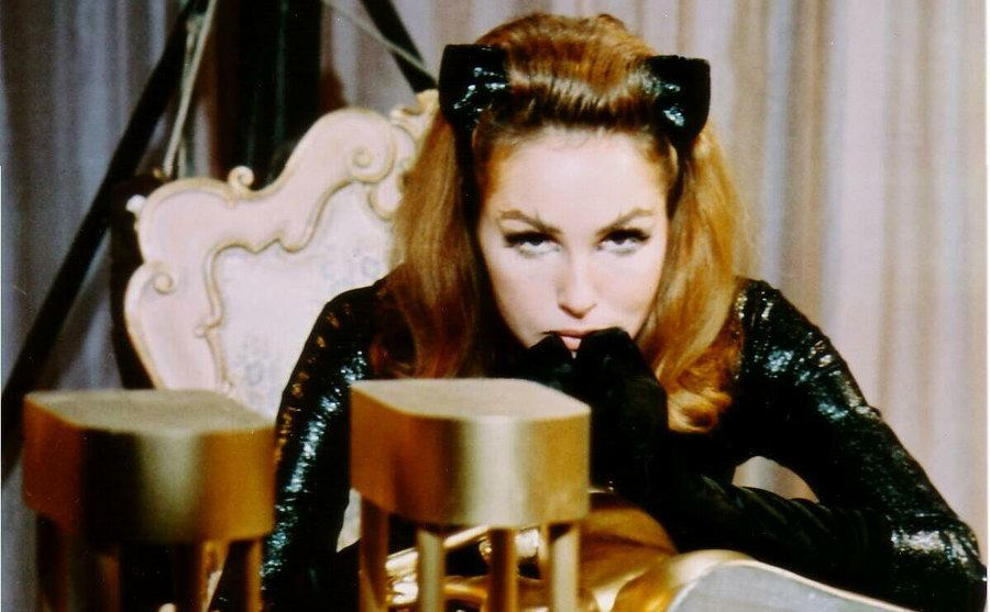 Julie Newmar is leaning on a table in her catsuit.