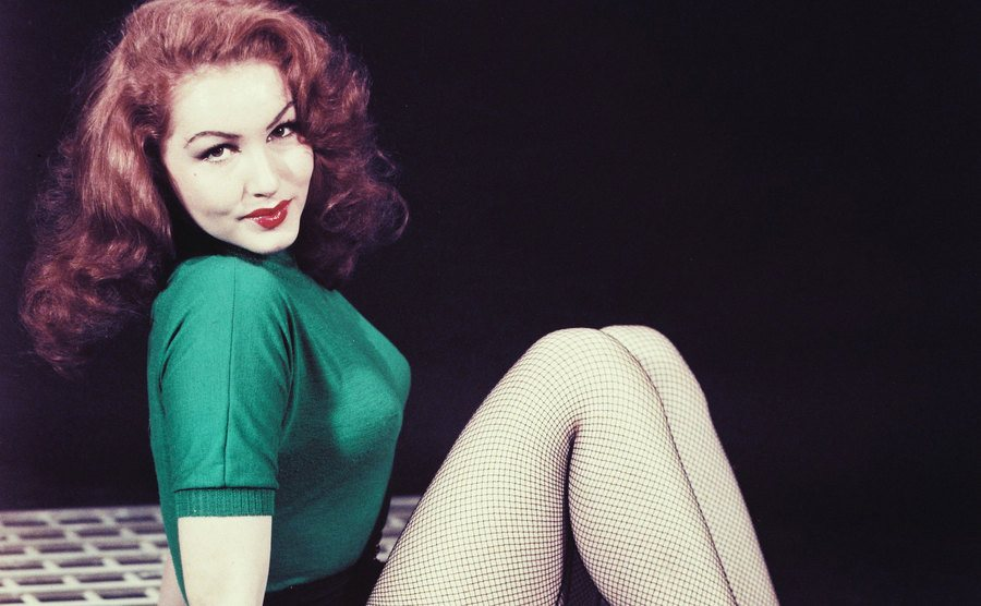 Julie Newmar is wearing a green short-sleeved woolen top and fishnet stockings.