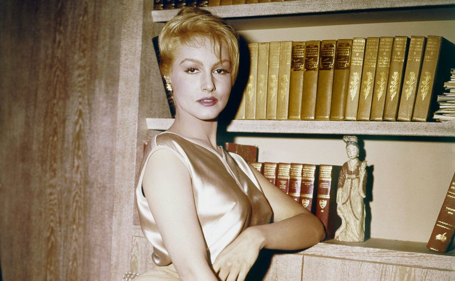 Julie Newmar is posing in a gold-colored outfit.