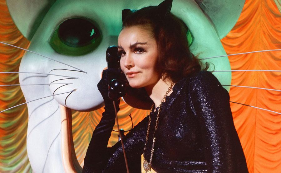 Julie Newmar as Catwoman holding a phone to her ear.