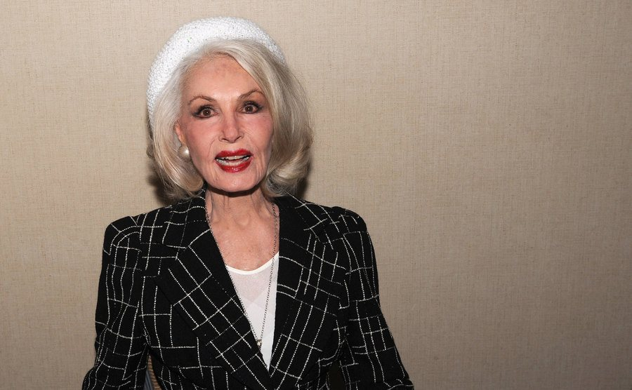Julie Newmar is wearing a tailored jacket and a white beret.