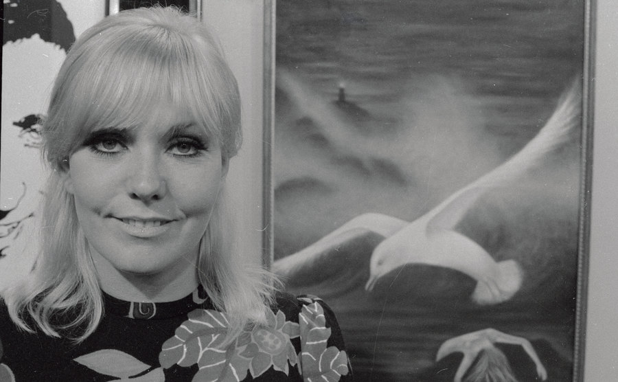 Kim Novak stands next to one of her paintings.