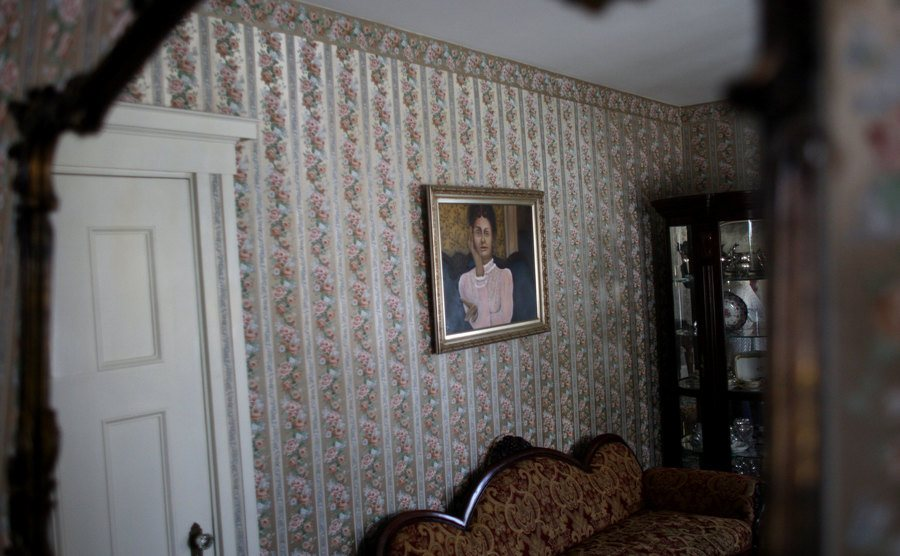 A portrait of Lizzie Borden hangs on a wall of her house.