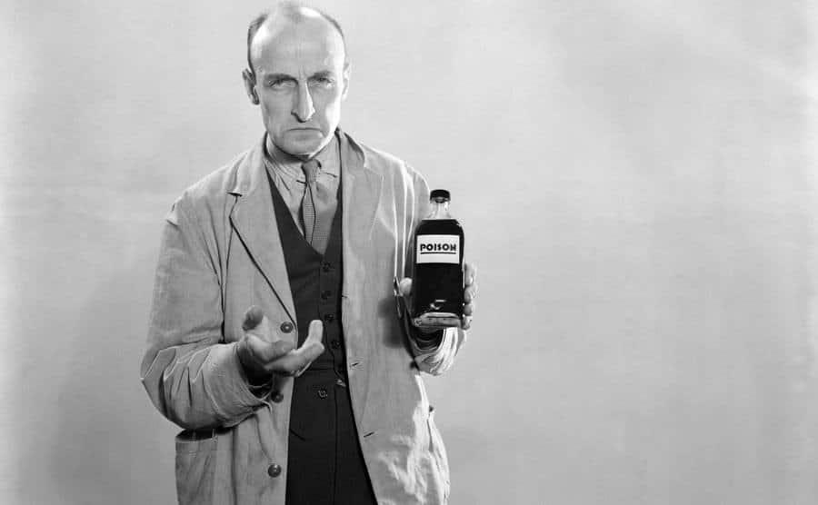 A man holds a poisonous bottle.