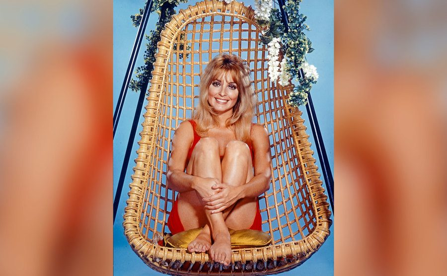 Sharon Tate sitting in a swing-chair.