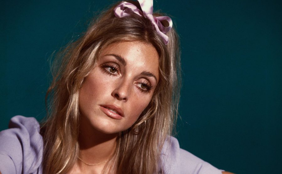 Sharon Tate with a solemn look and a pink bow in her hair.