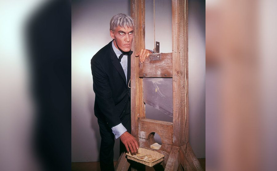 Ted Cassidy, as Lurch, stands over a guillotine.
