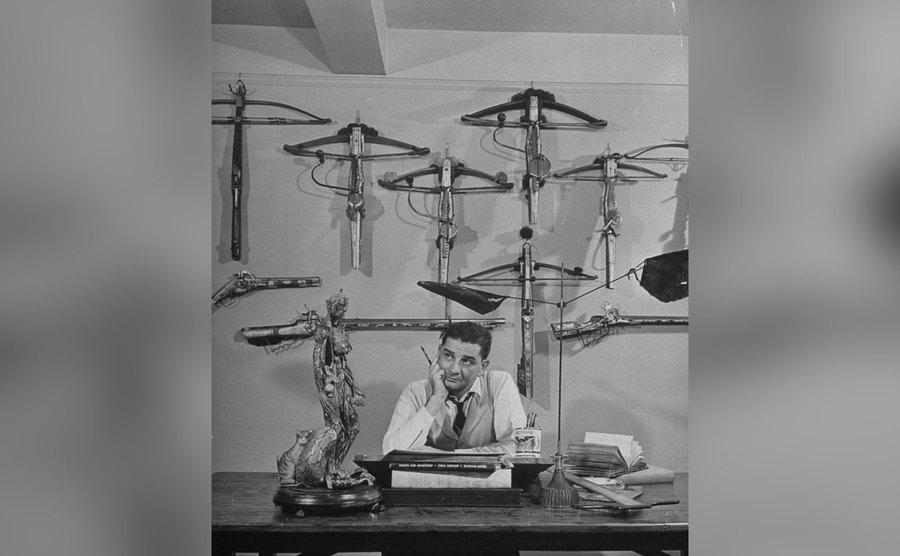 Charles Addams sits at his desk drawing; Crossbows hang on the wall behind him.