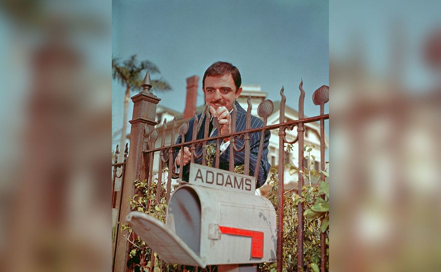 John Astin, as Gomez Addams, is sharpening the spikes of his front fence.