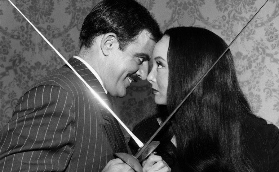Gomez and Morticia Addams are fencing.