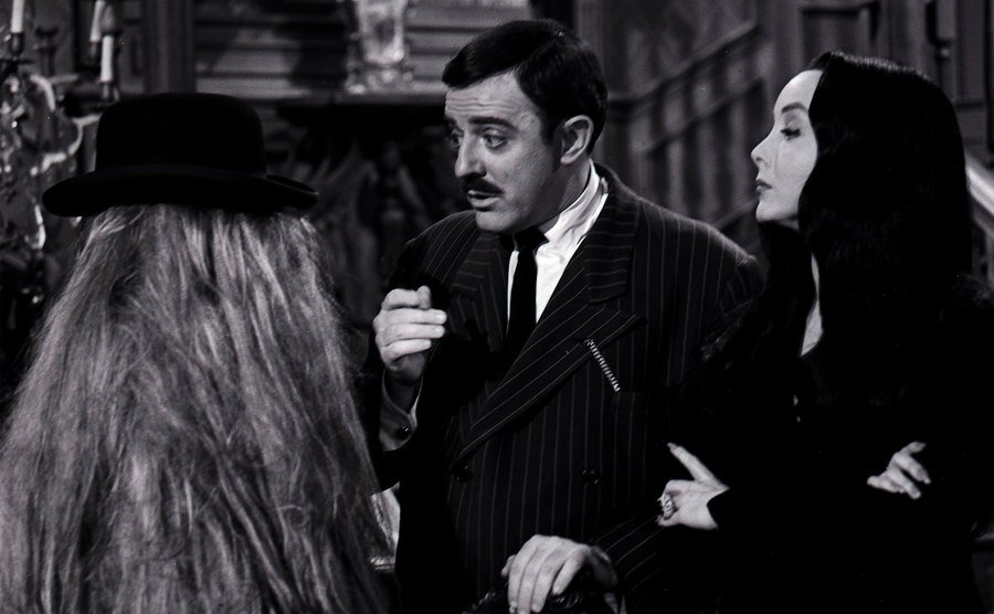 Gomez, Morticia, and Cousin Itt in a scene from The Addams Family.