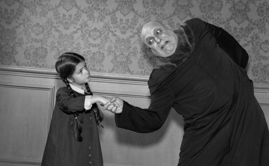 Uncle fester getting his arm twisted by little Wednesday.
