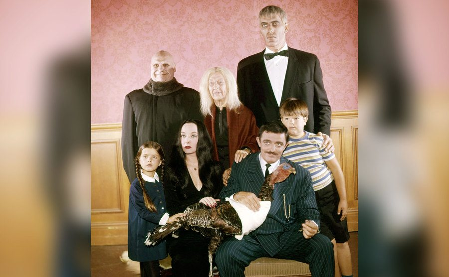 The cast of The Addams Family poses with a stuffed turkey.