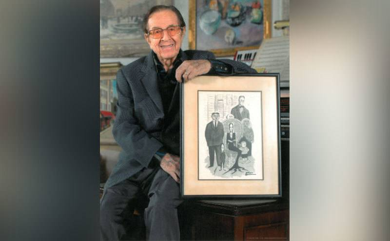 Vic Mizzy poses with a framed drawing of Charles Addams' Addams Family.