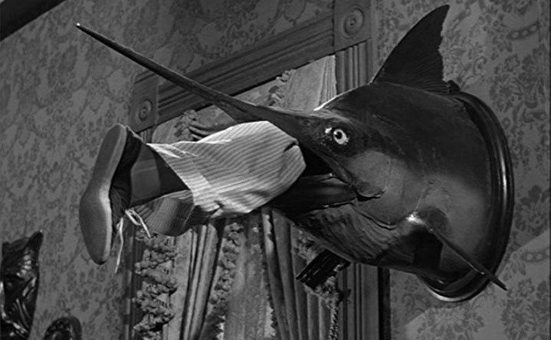 The swordfish head with a human leg coming out of the mouth hands on the wall.