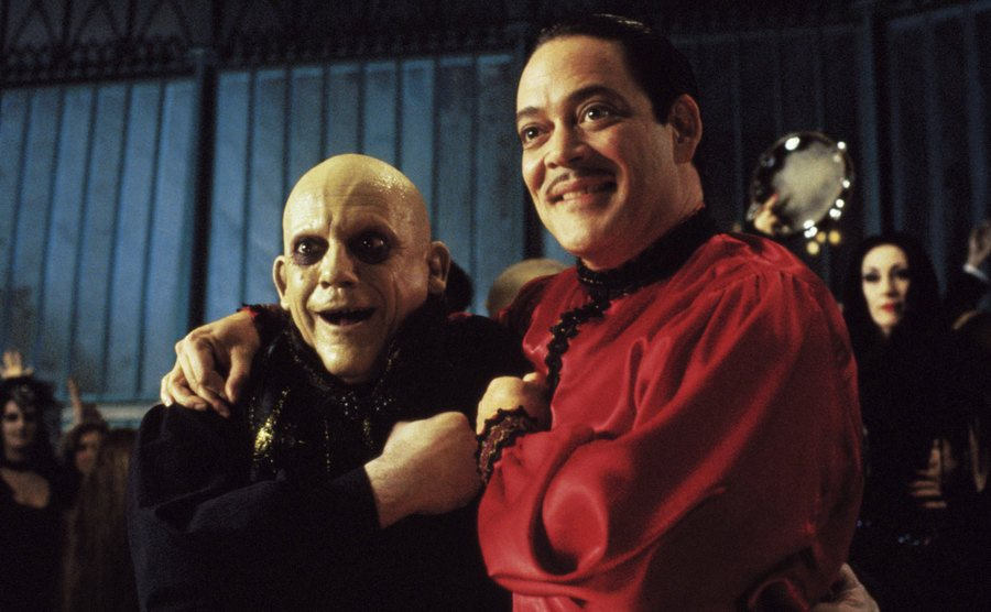 Christopher Lloyd, as Fester, embraces his brother Gomez, played by Raúl Juliá.