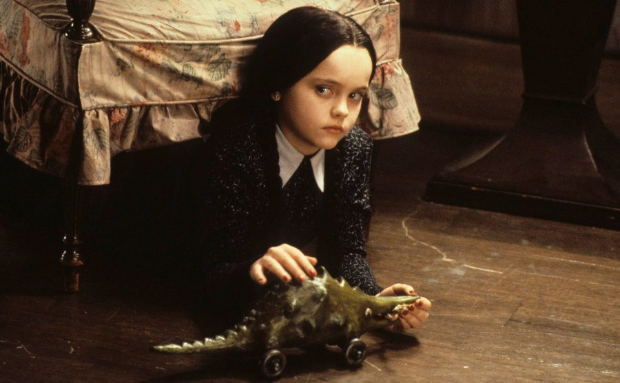 Christina Ricci, as Wednesday Addams, plays with her toys as she hides under the furniture.