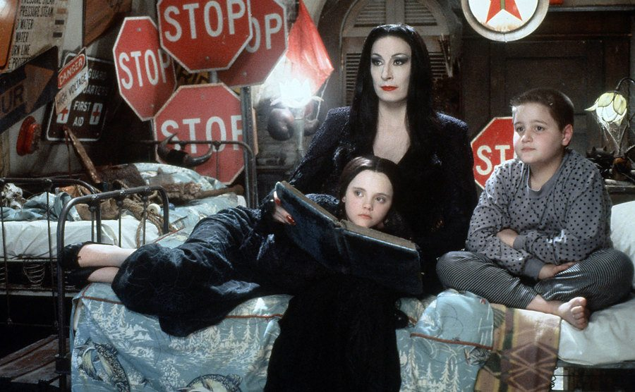 Morticia is reading a bedtime story to her kids in a scene from The ADDAMS Family Film.