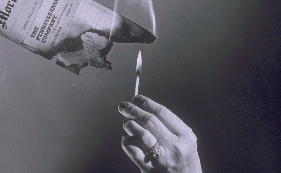 Burning paper with a match.
