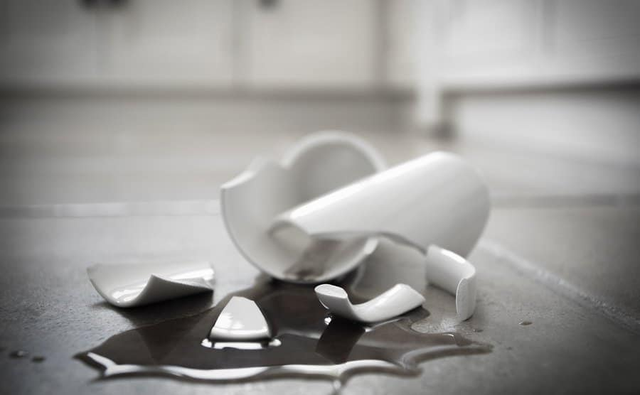 A broken coffee mug and spilled coffee on the floor.