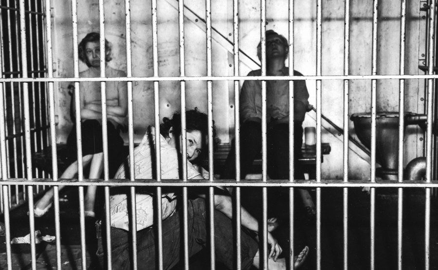 A picture of women sitting behind prison bars.