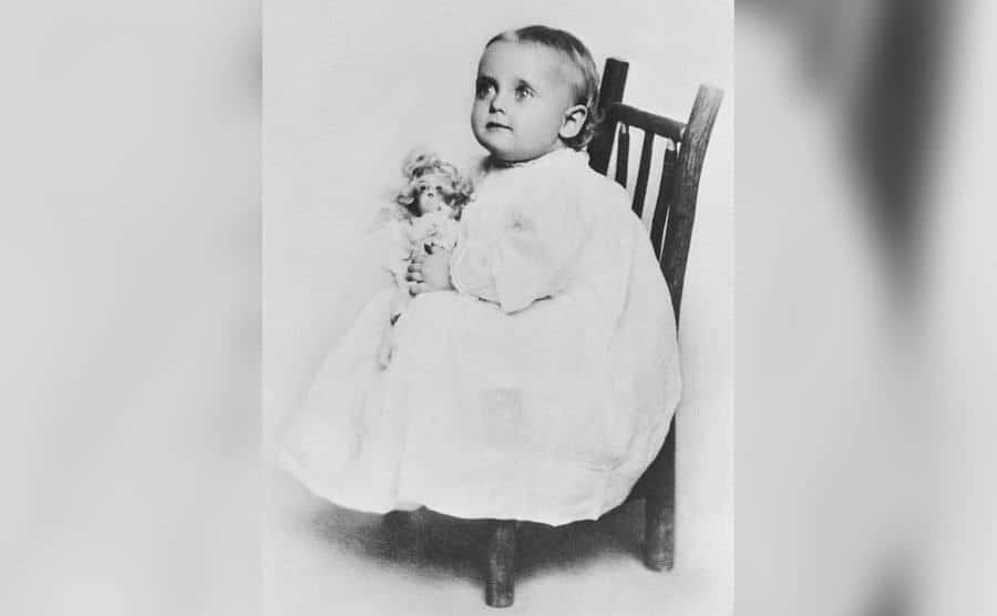 One-year-old Carole Lombard firmly grasps her doll as her picture is taken.