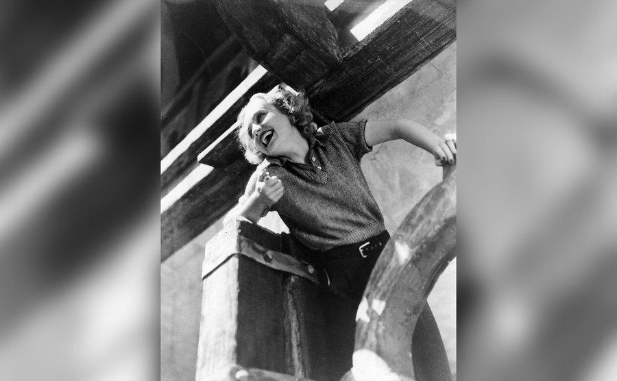 Carole Lombard is leaning on timbers on set.