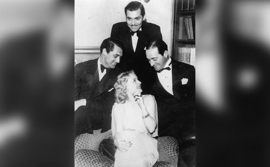 Carole Lombard is surrounded by Cary Grant, Clark Gable, and Ricardo Cortez.