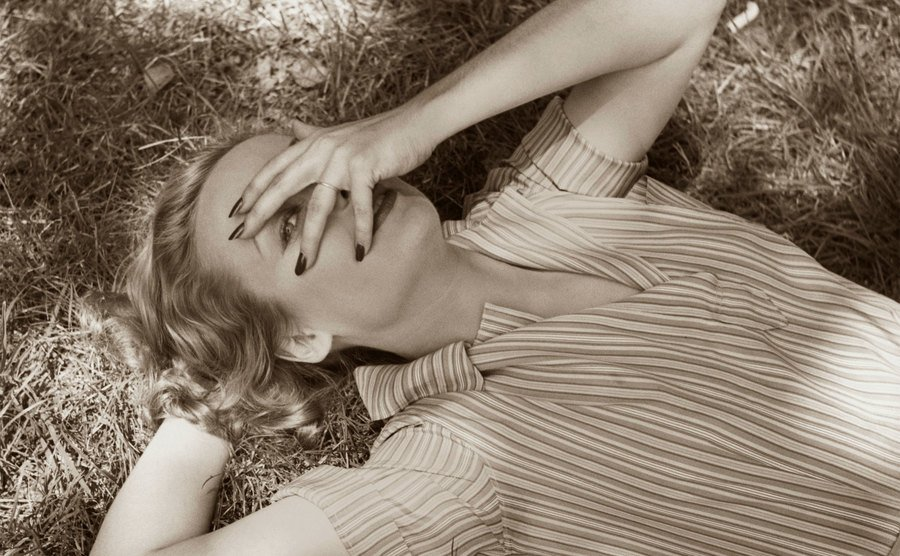 Carole Lombard is covering her face.