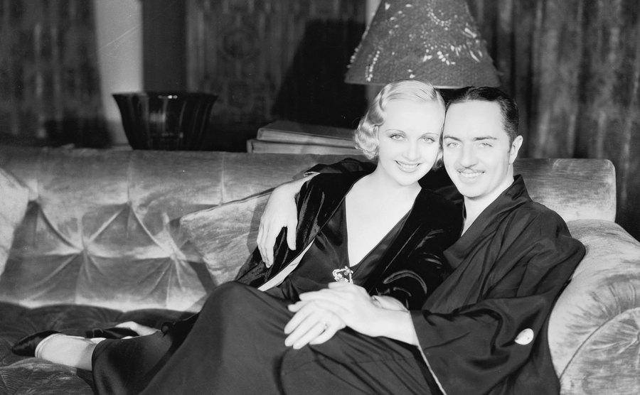 Carole Lombard and William Powell pose together on the couch.